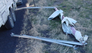 Photo of a ripped-off awning laying beside the fifth-wheel trailer.
